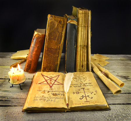 necromancy: Halloween still life of old books with Necronomicon and candles Stock Photo