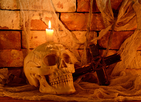deadman: Creepy human skull with candle and wooden cross on stone background in the dark