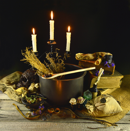 wiccan: Halloween still life with witch cauldron, burning candles and magic objects on black