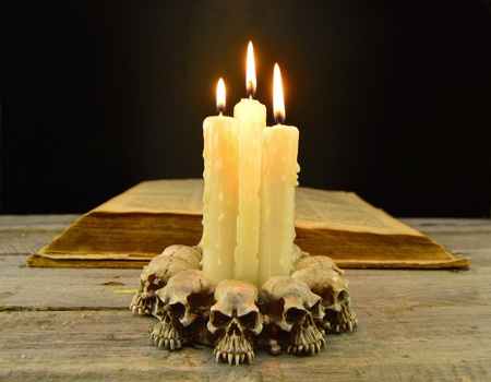 necromancy: Evil candles with old book on black background