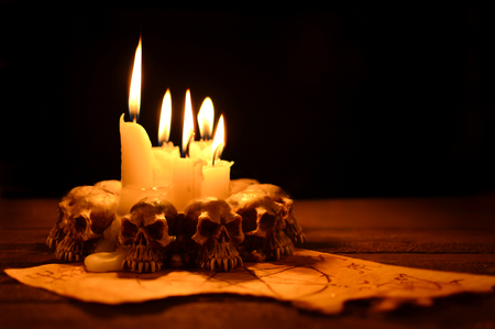 Evil candles on wooden background in the darkness