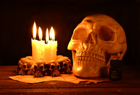 deadman: Creepy human skull with evil candles burning on wooden background in the darkness Stock Photo