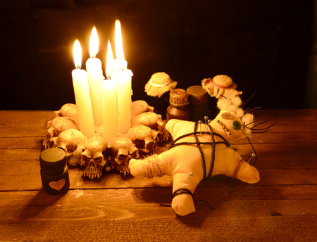 Voodoo doll with love potion bottles in candle light
