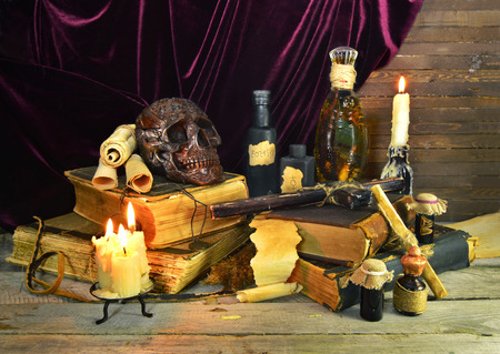 necromancy: Halloween still life with old books and warlocks magic objects on the wooden table