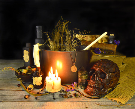 Halloween still life with witch cauldron, burning candles and magic objects on black photo