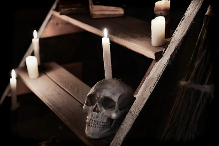 witchcraft: Mystic witchcraft ritual with scary skull and evil candles on wooden staircase. Occult or esoteric still life with magic objects, scary Halloween background