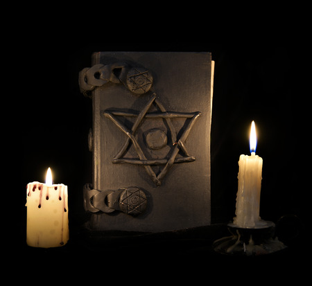 rite: Black magic book with pentagram in the darkness. Halloween concept, black magic ritual or spell with occult and esoteric symbols, divination rite. Vintage objects on table