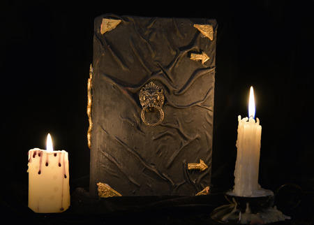 rite: Mystic still life with black magic book and two burning candles. Halloween concept, black magic ritual or spell with occult and esoteric symbols, divination rite. Vintage objects on table
