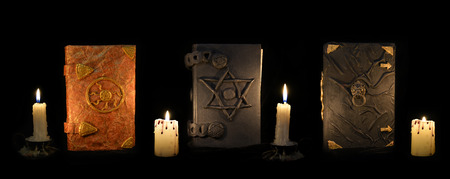 black magic: Three black magic books with burning candles in the darkness. Esoteric and occult objects on witch, divination ritual or Halloween concept. Mystic background