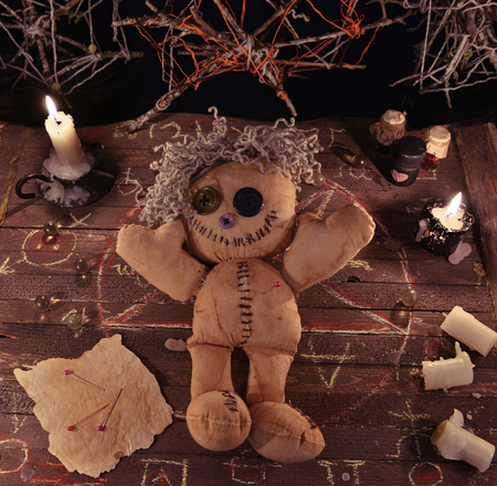 rite: Voodoo ritual with doll, candles and vintage objects on wooden table. Halloween background, black magic rite or spell with occult and esoteric symbols Stock Photo