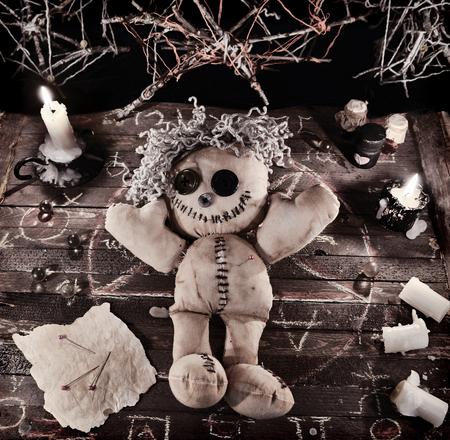 Voodoo-Ritual mit Puppe und magische Gegenstände im Vintage-Grunge-Stil. Halloween Hintergrund, schwarze Magie Ritus oder Zauber mit okkulten und esoterischen Symbolen.