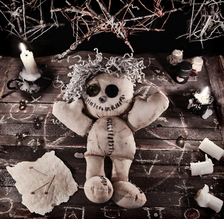 rite: Voodoo ritual with doll and magic objects in vintage grunge style. Halloween background, black magic rite or spell with occult and esoteric symbols.