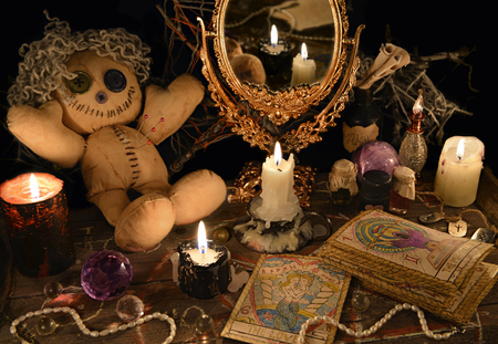 Magic ritual with voodoo doll, mirror, candles and tarot cards. Halloween concept, mystic or divination spell with occult and esoteric symbols. Vintage objects on witch table Reklamní fotografie - 71577198