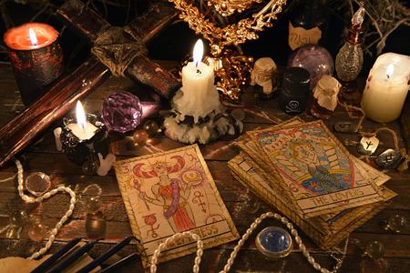 タロット カード、ビンテージのオブジェクト、クロスやキャンドルで神秘的な儀式。ハロウィーンのコンセプト、黒魔術や占いの神秘的な秘密のシ