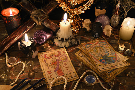 Mystic ritual with tarot cards, vintage objects, cross and candles. Halloween concept, black magic or fortune telling rite with occult and esoteric symbols. Astrology divination theme Stockfoto
