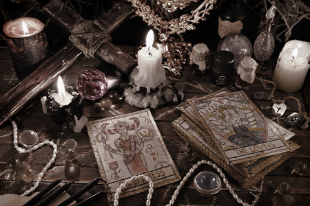 Mystic ritual with tarot cards, vintage objects and candles in grunge style. Halloween concept, black magic or fortune telling rite with occult and esoteric symbols. Astrology divination theme