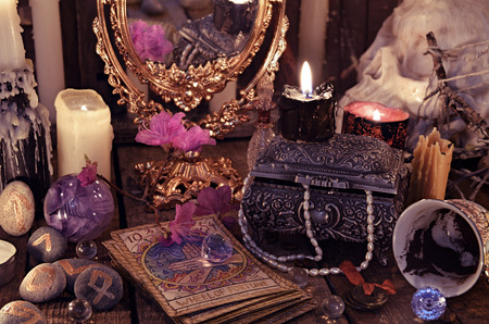 Divination rite with the tarot cards, flowers and mystic objects. Halloween background, black magic ritual or spell, occult and esoteric objects on witch table