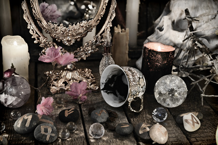 Close up of mystic objects, skull and pink flowers. Halloween background, coffee reading ritual, occult and esoteric objects on witch table