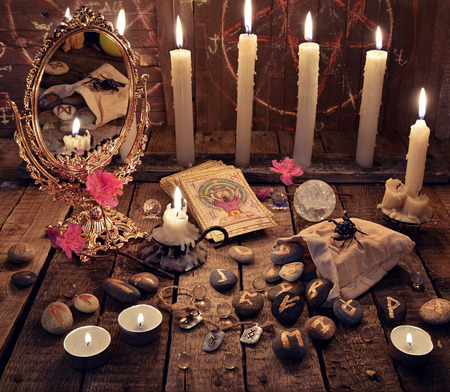 Mystic ritual with burning candles, magic mirror, flowers and the tarot cards. Halloween background, black magic rite or spell, occult and esoteric objects on witch table 스톡 콘텐츠