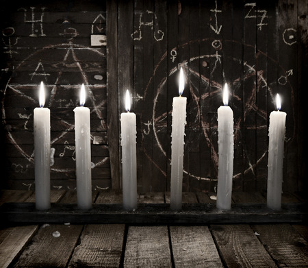 Still life with burning candles on wooden background with pentagram. Halloween background, black magic rite or spell, occult and esoteric objects on witch table 스톡 콘텐츠