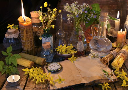 Still life with old book, candles, glass bottles and healing herbs. Alternative medicine vintage concept