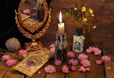 タロット カード、鏡、花、キャンドルのあるビンテージ静物。ハロウィーンのコンセプト、黒魔術や占いの神秘的な秘密のシンボルの儀式。占星術 写真素材