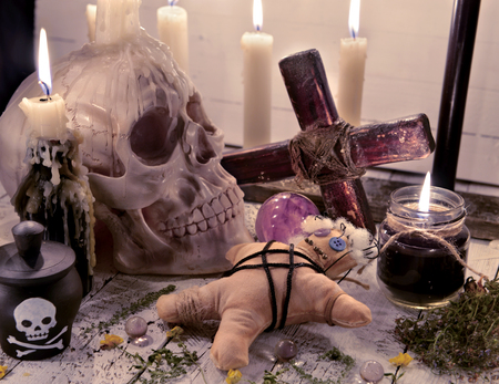Voodoo still life with skull, doll and burning candles. Halloween concept. Mystic background with occult and magic objects on witch table