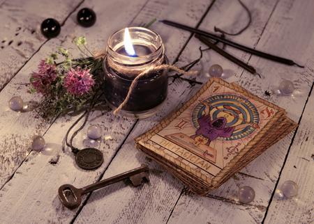 Schwarze kerze und alte tarotkarten auf hölzernen planken. Halloween und Wahrsagerei Konzept. Mystischer Hintergrund mit okkulten und magischen Gegenständen auf Hexentisch Standard-Bild