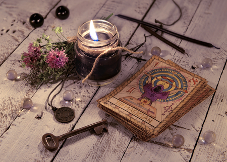 Black candle and old tarot cards on wooden planks. Halloween and fortune telling concept. Mystic background with occult and magic objects on witch table Stockfoto
