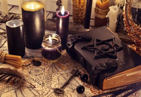 Zwart magieboek met zwarte kaarsen en demonenpapier. Halloween concept. Mystieke achtergrond met occulte en magische voorwerpen op heksen tafel