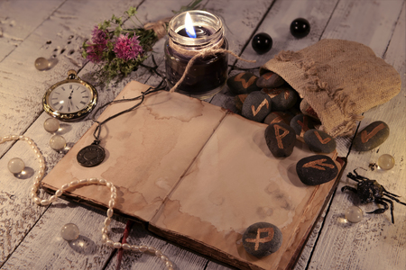 Old diary with black candles, ancient runes and clock on wooden planks. Halloween concept. Mystic background with occult and magic objects on witch table