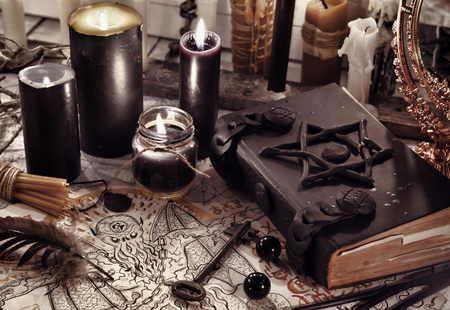 Toned still life with black magic book, demon paper and black candles. Halloween concept. Mystic background with occult and magic objects on witch table Banco de Imagens