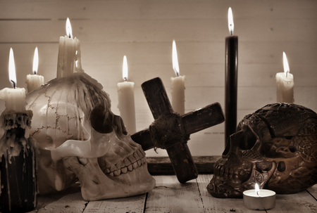 Still life with two scary skulls, black candle and cross. Halloween and voodoo concept. Mystic background with occult and magic objects on witch table
