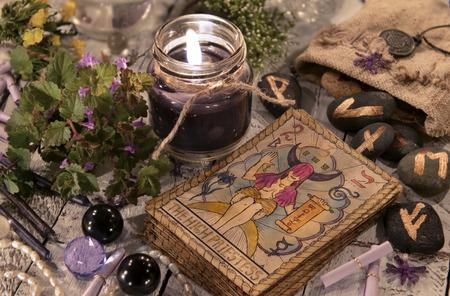 타로 카드와 룬이있는 검은 색 촛불. 할로윈과 재산 개념을 말하는입니다. 마녀 테이블에 신비로운 배경과 신비로운 마술 개체