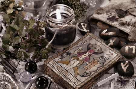 Toned still life with black candle, runes and the tarot cards. Halloween and fortune telling concept. Mystic background with occult and magic objects on witch table Stock Photo