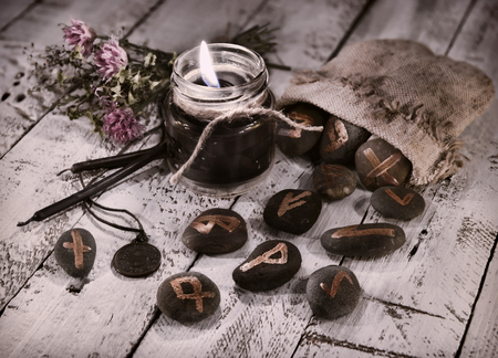 Toned still life with black candles and runes. Halloween and fortune telling concept. Mystic background with occult and magic objects on witch table