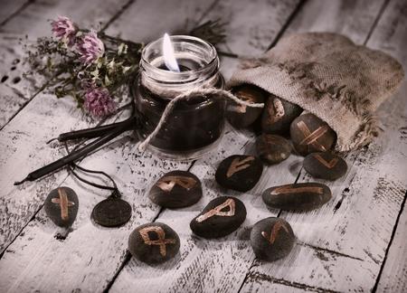 Tonos de naturaleza muerta con velas y runas negras. Halloween y la fortuna que dice el concepto. Fondo místico con objetos ocultos y mágicos en la mesa de la bruja Foto de archivo - 81338730