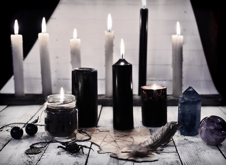 occultism: Mystic still life with black candles and pentagram on paper. Halloween concept. Mystic background with occult and magic objects on witch table