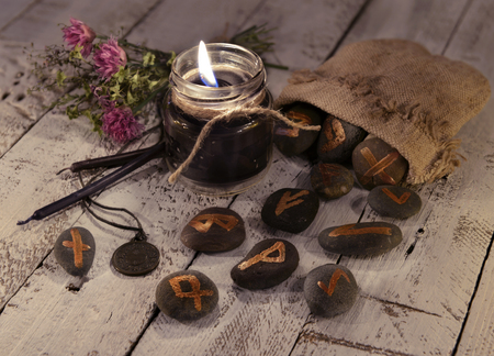 supernatural: Fortune telling still life with black candles and ancient runes on stones. Halloween concept. Mystic background with occult and magic objects on witch table