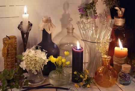 Bougies, bouteilles en verre, pots et fleurs sur la table. Médecine alternative, ancien concept pharmaceutique et homéopathique. Nature morte mystique et occulte, antécédents médicaux vintage