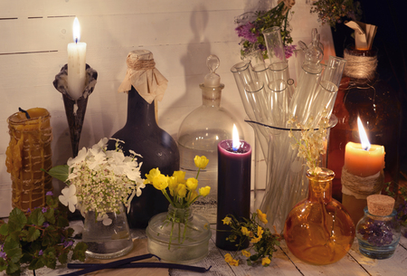 Candles, glass bottles, jars and flowers on the table. Alternative medicine, old pharmaceutic and homeopathic concept. Mystic and occult still life, vintage medical background