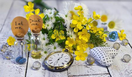 elixir: Los relojes de bolsillo de la vendimia, las botellas minúsculas con las etiquetas me beben, me comen, y las bolas cristalinas en tablones. Alicia en el fondo del país de las maravillas, concepto abstracto del cuento de hadas con las flores del verano