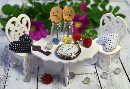 Tiny vintage objects - bottles, clock, key - on small table with white chairs and wild roses behind. Alice in Wonderland background, fairy tale abstract concept with summer flowers
