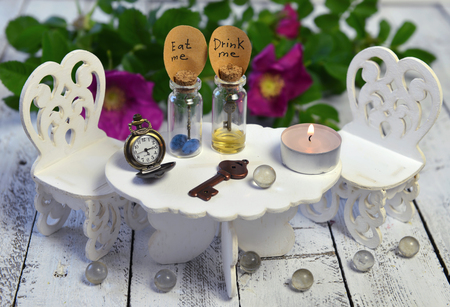 drink me: Tiny table with chairs and two bottles with tags eat me, drink me. Alice in Wonderland background, fairy tale abstract concept with summer flowers