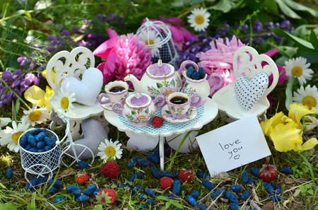 bebes lindos: Small dishware with vintage objects, note with text love you, berries and flowers. Mad tea party concept. Beautiful greeting card with summer flowers and vintage objects. Fairies in the garden