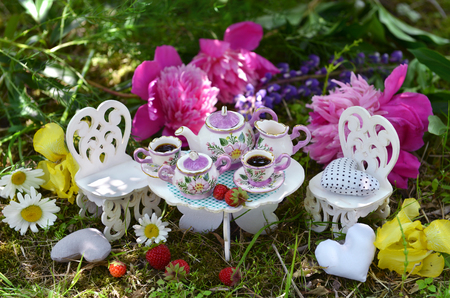 Cute dishware on small table with toy chairs and flowers in the garden. Mad tea party concept. Beautiful greeting card with summer flowers and vintage objects. Fairies in the garden