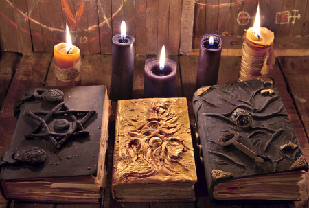Three magic books with burning candles on planks. Mystic still life with scary occult objects, horror Halloween and black magick concept, fortune telling or divination rite