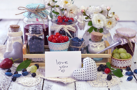 Note with text love you, fresh berry and jam in vintage glass jars. Making fruit jam concept. Fresh berry on wooden table, summer still life and rustic food vintage background. Preserved fruits
