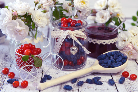 Wooden spoon full of honey berry, vintage jars with fresh berry and jam. Making fruit jam concept. Fresh berry on wooden table, summer still life and rustic food vintage background. Preserved fruits