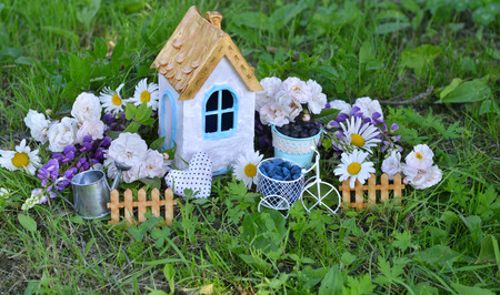 Beautiful house with wildflowers, fence and watering can. Lovely miniature house for greeting cards, wedding or birthday concept, real estate, downsizing, home ownership. Vintage summer background